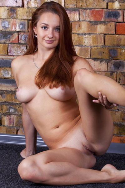 Sexy redhead sits naked on the floor and shows off her tan lines