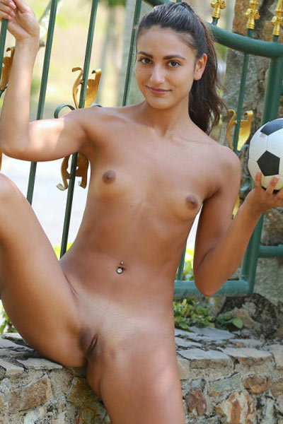 Cira Nerri plays with a soccer ball in the park while wearing nothing but sneakers
