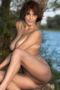 Veralin with sexy tan lines poses nude with tree by the lake