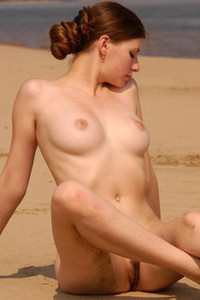 Gorgeous Polena sits on sand and shows off trimmed pussy and big boobs