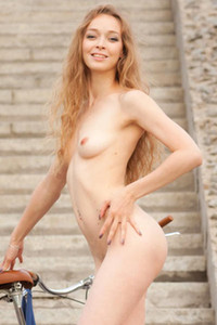 Eugena rides her bike topless while giving a great view up her skirt