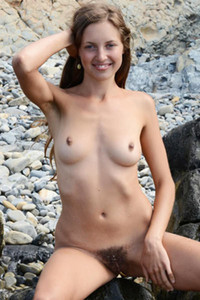 Young sexy blonde sits naked on rocks and shows off her full bush