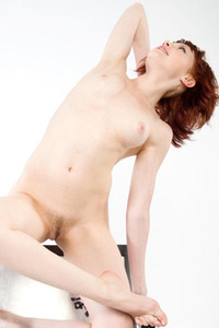 Young redhead sits cross legged in chair while completely naked