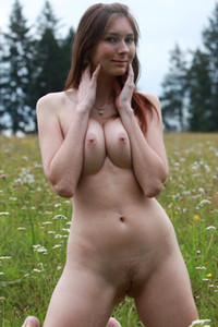 Cute young brunette spreads herself with her fingers while naked in grass
