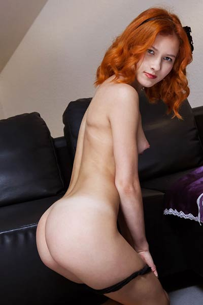 Hot redhead touches her puffy pussy on a black leather couch