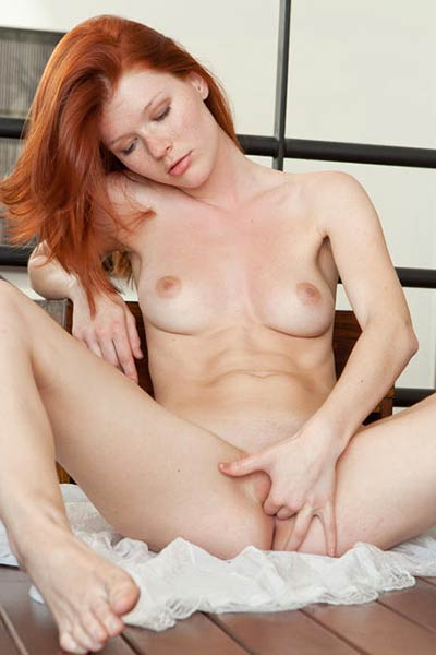 Gorgeous redhead spreads her legs wide while naked on the floor