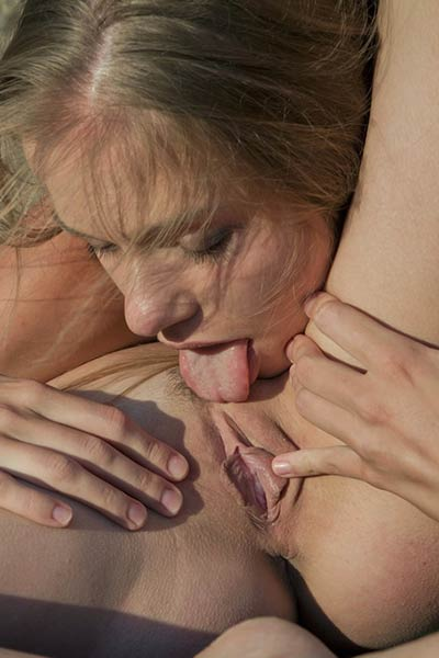 Two skinny lesbians caress each others bodies with their mouths in public