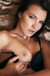 Sexy brunette seductively poses on a large brown velvet couch