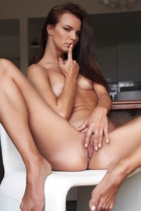 Slender sexpot with raven hair and seethrough black leotard poses luridly on dining table