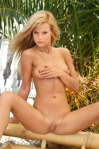 Naked and tan young blonde Miela A spreads her pussy in a tropical setting