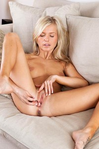 Bella C is naked on the sofa with her legs spread wide open