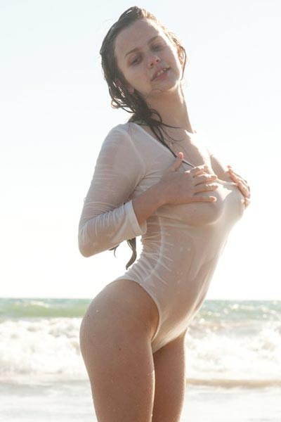 Hot brunette gets her swimsuit wet and see-through at the beach