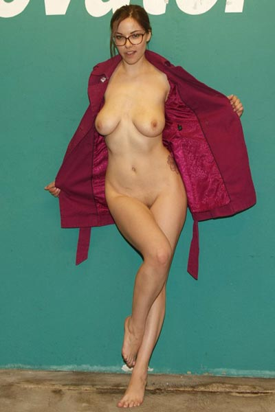 Gorgeous brunette opens up her coat to show her naked body underneath in public