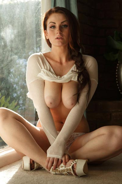 Emmy Sinclair lifts up her shirt to show off perfect breasts near window