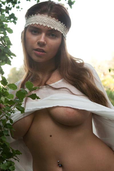 Hot brunette peels open her shirt to show her breasts in the woods