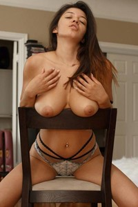 Sexy brunette kneels on chair and shows off her naked breasts