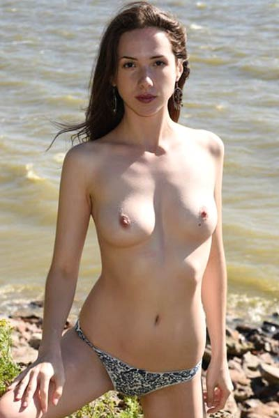 Dirty Dama poses outside by the sea revealing her perky tits and ass