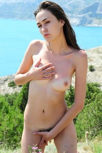 Lusty Lili poses outdoors by the sea revealing her trimmed bush and ass