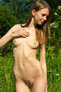Russian Elise poses in a field showing her juicy pussy for your pleasure