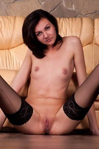 Teen brunette Nancy with her nice tits and pierced nipples poses in black stockings