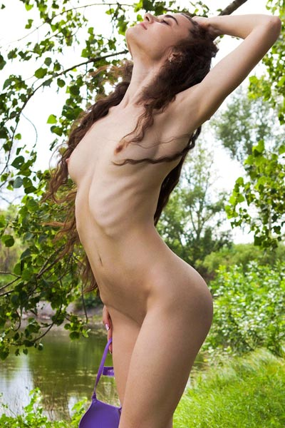 Naughty Erika Rose poses near a creek showing off her sweet pussy