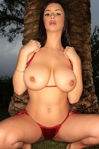 Newbie girl reveals her big tits by a palm tree for your pleasure