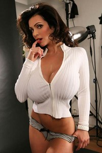 Classy Denise Milani models in white revealing her big breasts at home