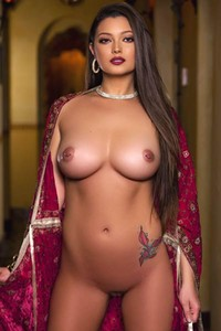 Majestic busty brunette with her mesmerizing eyes poses provocatively in royal room