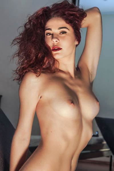 Redhead vixen Callista bares her hot curves as she poses seductively and eats chocolate