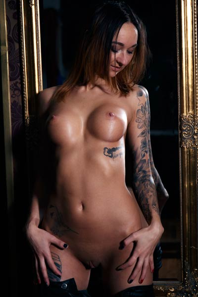 Tattooed babe Emma shows her nice tits and peachy ass for a photoshoot