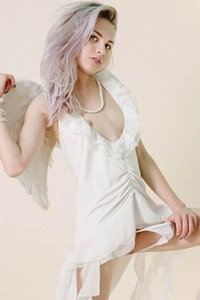 Pale skinned vixen poses naked in her sexy angel outfit for a magazine