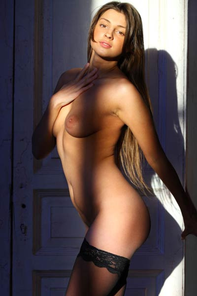 Adorable babe is posing naked wearing only her sexy black stockings