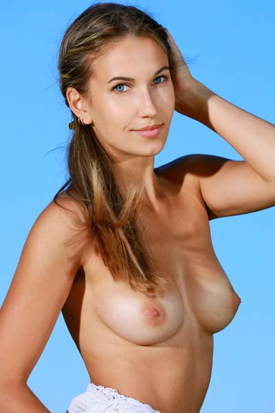 Beautiful Milenia with her teasing smile poses naked outdoor and presents her hot tan lines