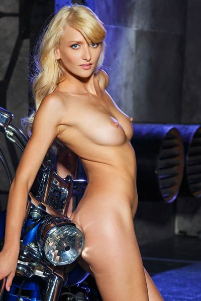 Platinum blonde bombshell poses provocatively by the motorcycle