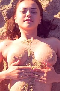 Relax on the beach with busty and naughty brunette Li Moon