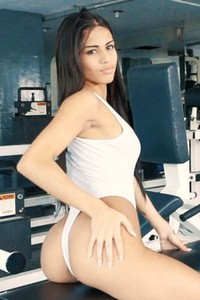 Irresistible tanned babe strips down her bodysuit in the gym and bares her perfectly shaped body