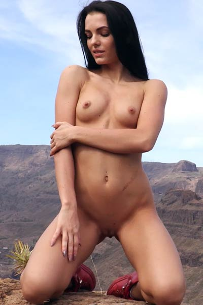 Tempting naughty babe spreads her tight pink pussy high in the mountains
