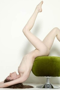 Young babe with smooth pale skin poses on green chair and bares her pink pussy and sweet round tits