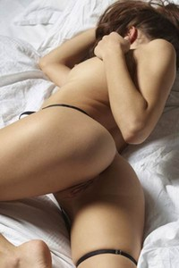 Horny and kinky brunette poses erotically on the bed and shows off her sex assets
