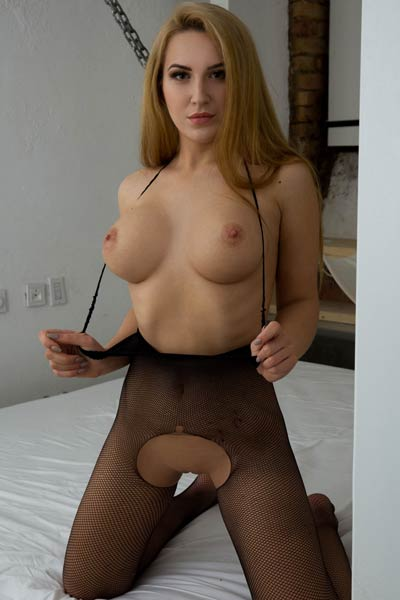 Breathtaking babe Sandy E uses her fingers to pleasure her tight and wet pussy in the bedroom