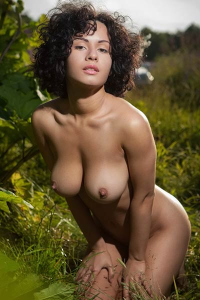 Exotic curly babe bares her sexy body and delectable big tits as she poses in nature