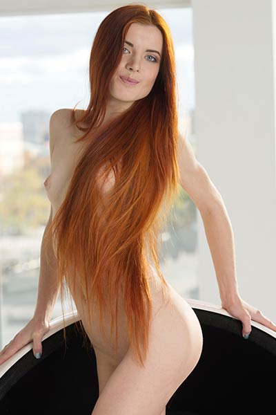 Redhead vixen Kiva with her mesmerizing eyes poses in stylish chair and bares her tight pale body