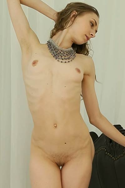 Lonely brunette with small titties and shaved pussy stretches her skinny body on the sofa