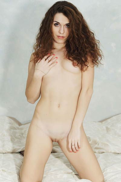 Sexy brunette with curly hair is not feeling shy to expose her all natural body