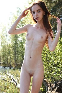 Cute skinny babe poses naked in the forest and presents her petite pale body