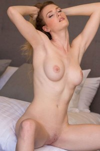 Stunning blonde Ashley Lane poses naked on the bed and dazzles us with her tall and tight body