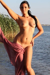 It is just a perfect day for this hot brunette to pose in nude by the sea
