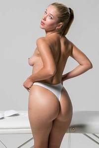 Beautiful blonde Xana D oils her skin and poses on the massage table showing her luscious body