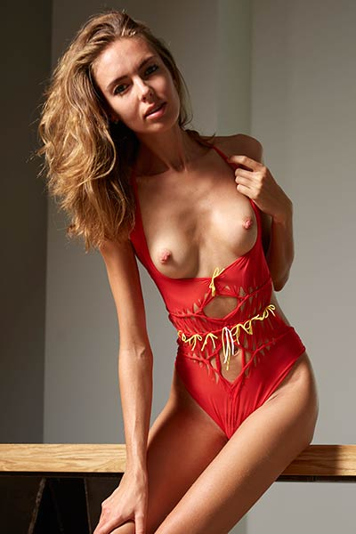 Slim brunette in sexy red swimsuit gets naked and naughty