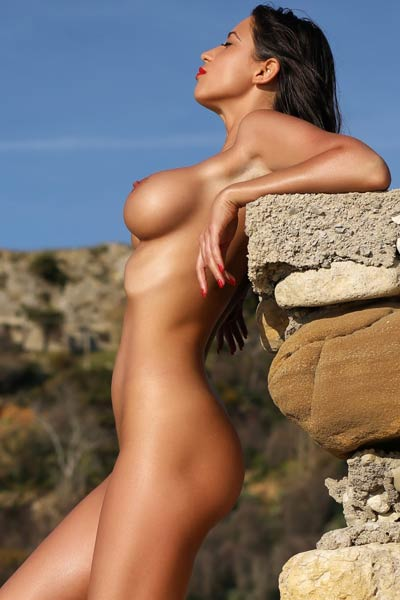 Her gorgeous naked body looks amazing as she enjoys relaxing on the beach